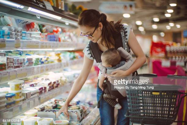 Pretty young mom carrying baby in baby carrier while shopping in a supermarket.