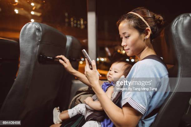 Pretty young mom carrying her baby in a baby carrier using a smartphone while riding on the bus.