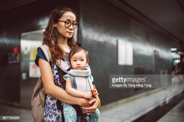 Pretty young mom carrying her baby in a baby carrier while waiting for train at the platform.