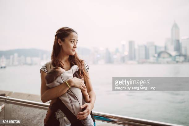 Pretty young mom carrying her sleeping baby in a baby carrier looking at the sea joyfully at the Victory Harbour Promenade