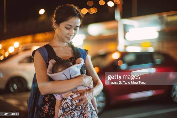 Pretty young mom carrying her sleeping baby in the baby carrier in the parking lot at night