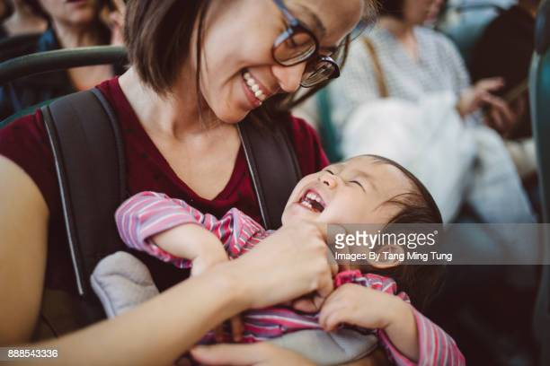 Pretty young mom carrying lovely little baby in a baby carrier in a bus while playing with her joyfully.