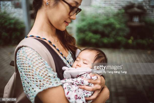 Pretty young mom carrying sleeping baby in a baby carrier while strolling on the street joyfully.