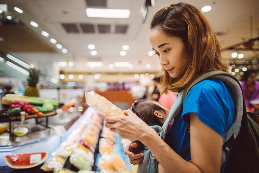 Pretty young mom checking product ingredients while doing grocery shopping in supermarket - gettyimageskorea