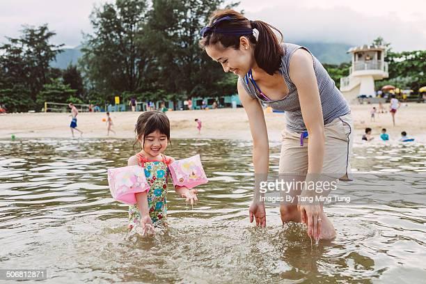 Pretty young mom & child playing in sea joyfully