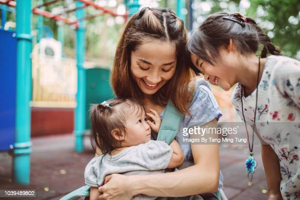 Pretty young mom enjoying quality time with her 2 little children in the playground joyfully.