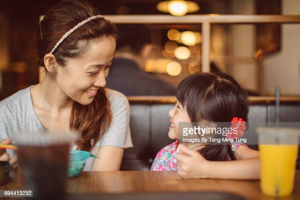 Pretty young mom enjoying quality time with her little daughter joyfully in a restaurant.