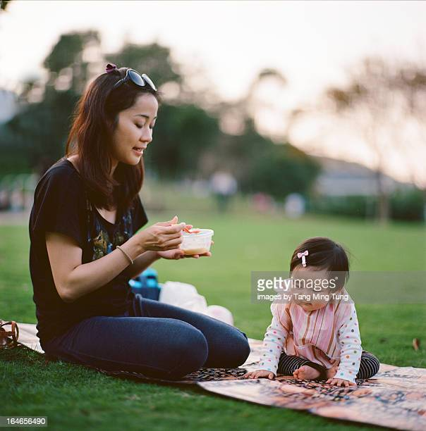 Pretty young mom feeding baby on a picnic blanket