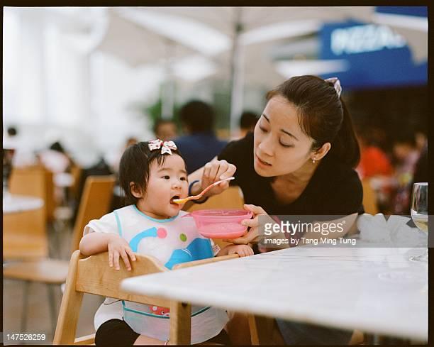 Pretty young mom feeding baby