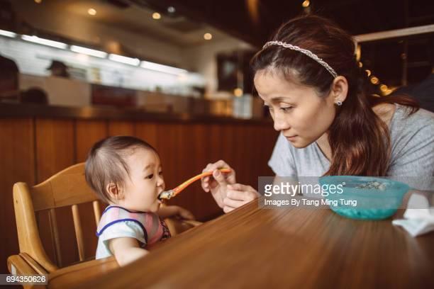 Pretty young mom feeding her baby in a restaurant joyfully.