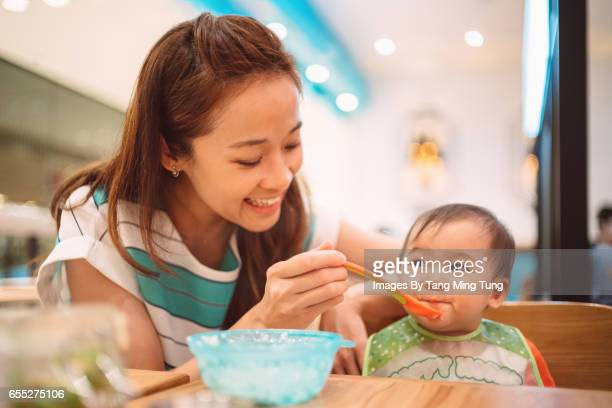 Pretty young mom feeding her lovely baby with baby food in a restaurant joyfully