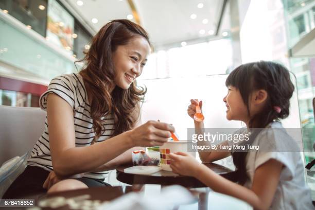 Pretty young mom having dessert with her lovely little daughter in a shopping mall joyfully