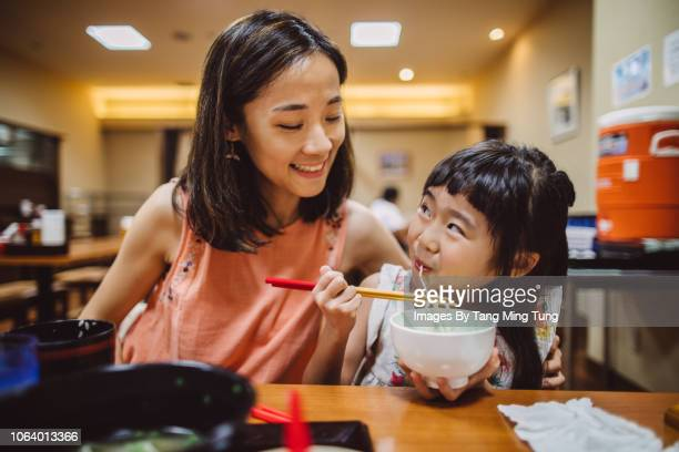 pretty young mom having meal joyfully with her lovely daughter in a japanese restaurant - japanese food stock pictures, royalty-free photos & images