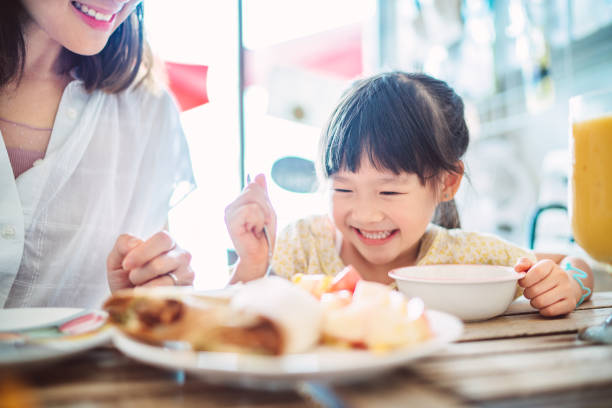 pretty young mom having meal joyfully with her lovely daughter in a restaurant - mom and child stock pictures, royalty-free photos & images