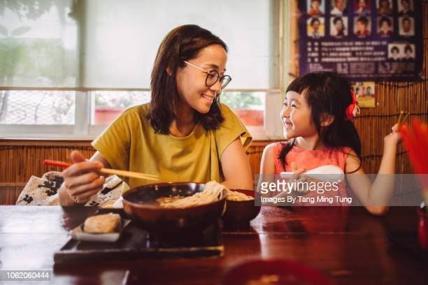 Pretty young mom having meal with her lovely daughter joyfully in Japanese restaurant