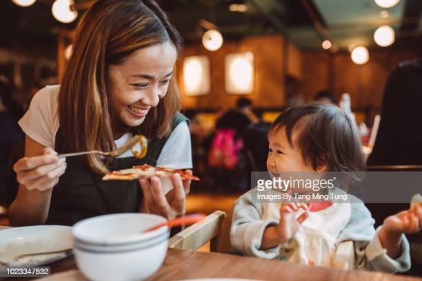 Pretty young mom having pizza with baby in a restaurant joyfully.