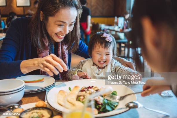 Pretty young mom having veggie salad with her lovely little daughters in a restaurant joyfully.
