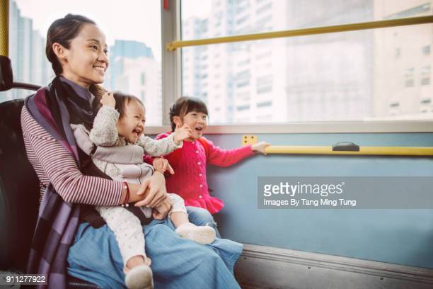 Pretty young mom, her lovely baby and daughter riding on a bus joyfully.