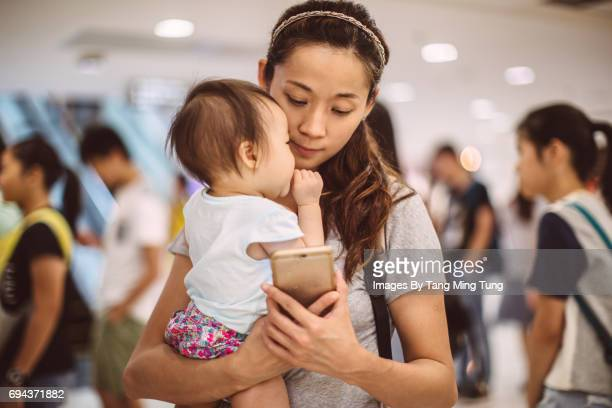 Pretty young mom holding a baby while using a smartphone