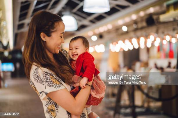 Pretty young mom holding her lovely baby girl in the arms while talking to her joyfully in the shopping mall