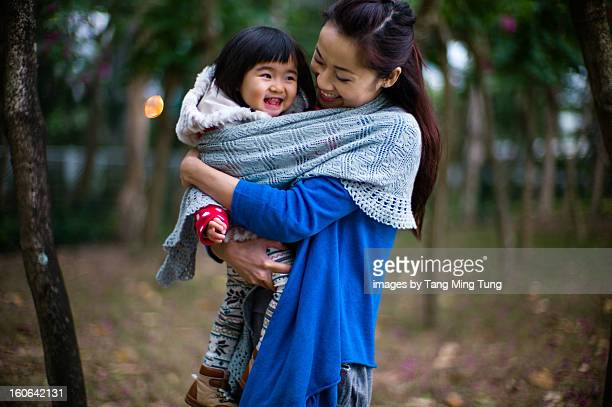 Pretty young mom holding laughing baby in a park