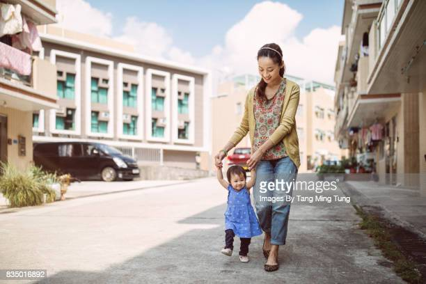 Pretty young mom holding lovely little baby's hands and teaching her to walk joyfully.