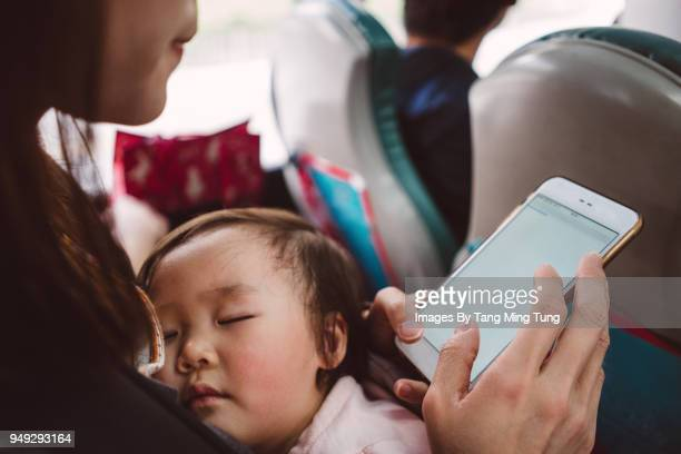 Pretty young mom holding sleeping baby while using a smartphone in a bus.