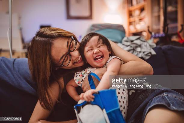 Pretty young mom hugging and playing with baby on the sofa joyfully