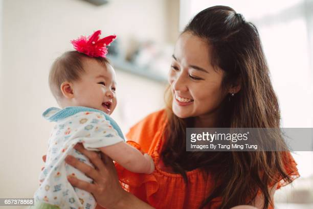 Pretty young mom hugging and playing with her little baby joyfully on the bed.