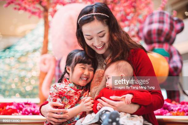 pretty young mom hugging her little daughter and her baby joyfully during chinese new year. - chinese new year stock pictures, royalty-free photos & images