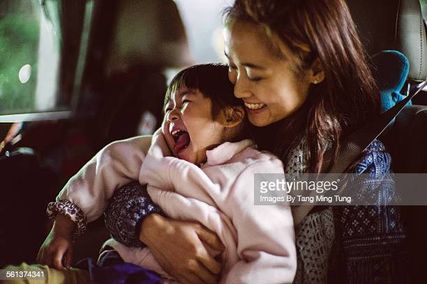 Pretty young mom hugging little daughter in car