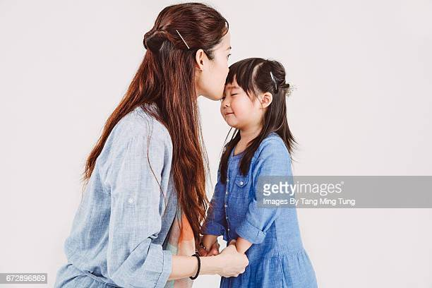 Pretty young mom kissing little daughter