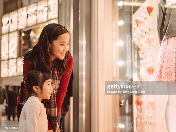 Pretty young mom & little daughter window shopping