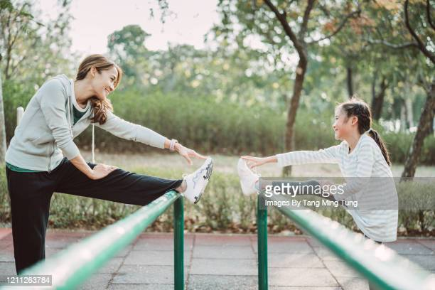 pretty young mom & lovely daughte stretching legs on rail in park joyfully - reaching stock pictures, royalty-free photos & images