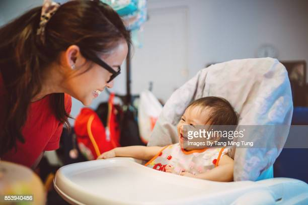 Pretty young mom playing with her lovely baby who's sitting in a baby highchair joyfully.