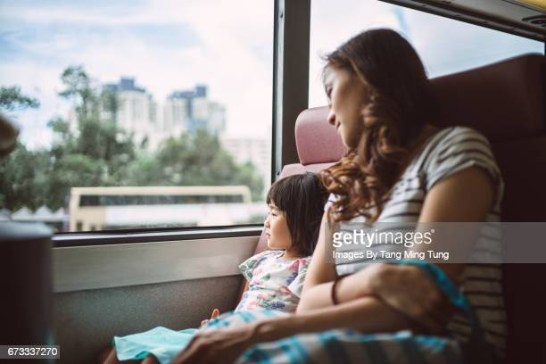 Pretty young mom riding a bus with her lovely little daughter joyfully
