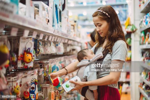 Pretty young mom shopping for baby products with her baby in department store.