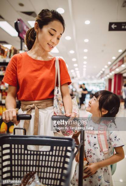 Pretty young mom shopping joyfully with her lovely daughter in supermarket
