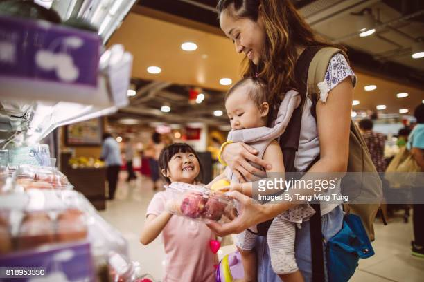 Pretty young mom shopping with her lovely little daughter in the supermarket joyfully while carrying her baby with a baby carrier.