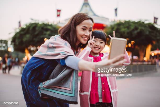 Pretty young mom taking selfies joyfully with her lovely little daughter in the theme park