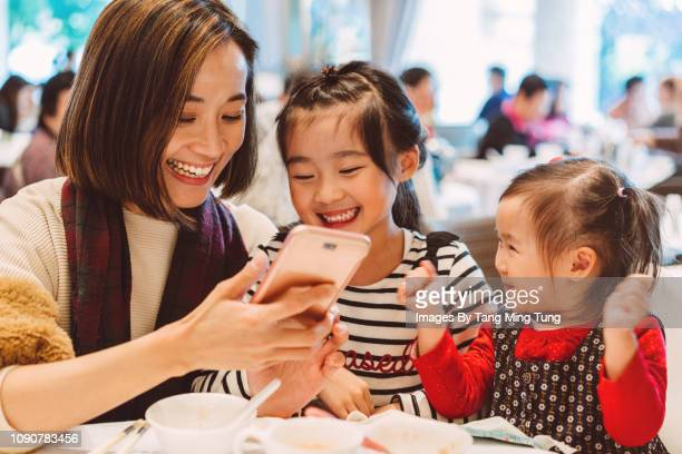 Pretty young mom taking selfies with daughters joyfully in a Chinese restaurant.