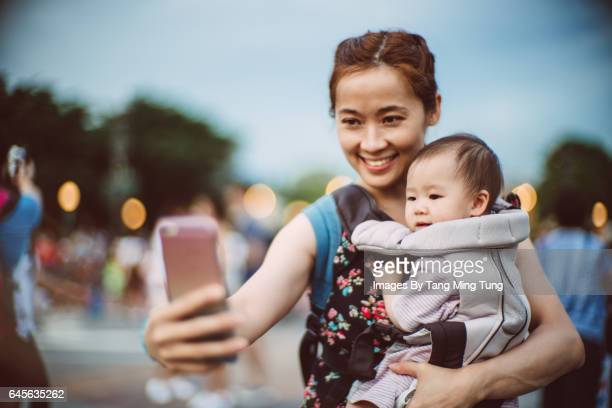 Pretty young mom taking selfies with her baby at the theme park joyfully