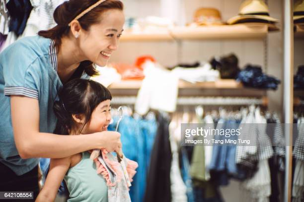Pretty young mom trying on clothes with her lovely little daughter in a fashion boutique joyfully.