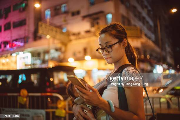 Pretty young mom using a smartphone on the street at night when carrying her baby in a baby carrier.