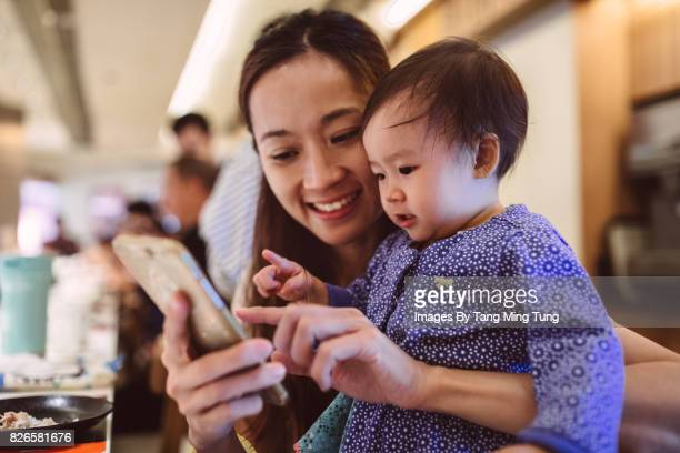 Pretty young mom using a smartphone with her baby joyfully in a Japanese restaurant.