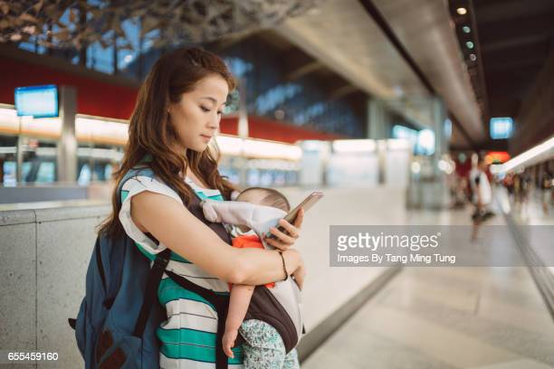 Pretty young mom using smartphone at the train platform while carrying her sleeping baby in a baby carrier.
