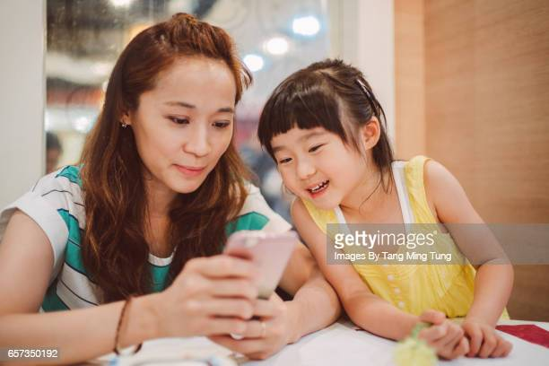 Pretty young mom using smartphone with her lovely little daughter in a restaurant joyfully.