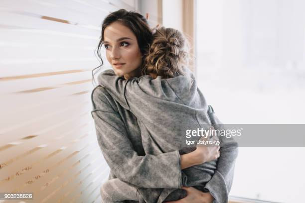 pretty young mother holding her lovely child - angst stockfoto's en -beelden