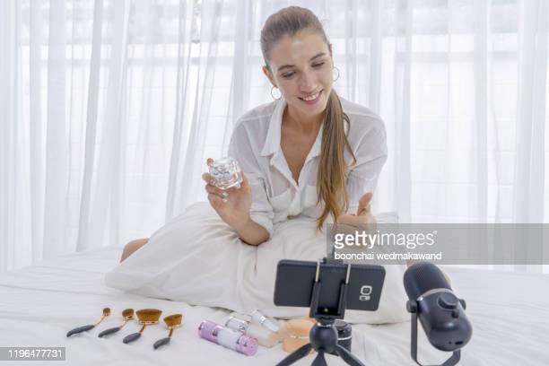 pretty young woman advertising cosmetics in blog - influencer stockfoto's en -beelden