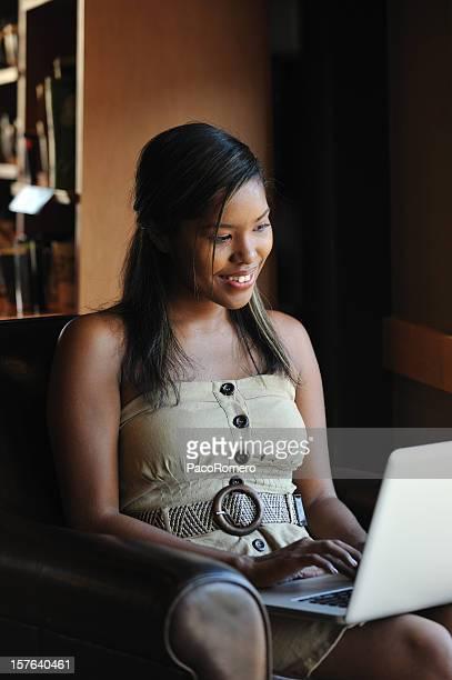 Jolie jeune femme sur un ordinateur par une fenêtre